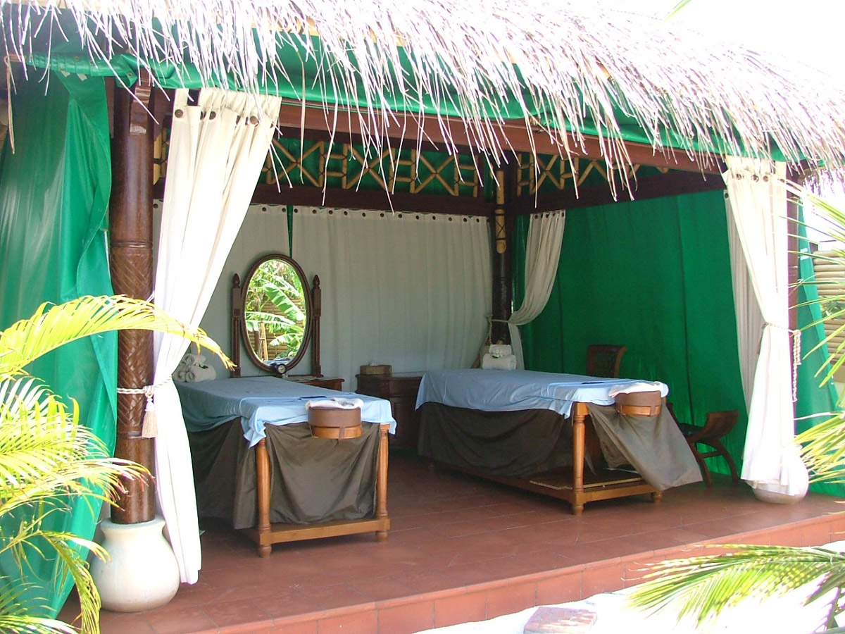 A spa area with two massage beds inside a an open hut