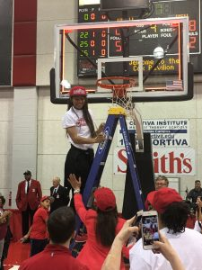 Teenager on top of a ladder at a basketball game