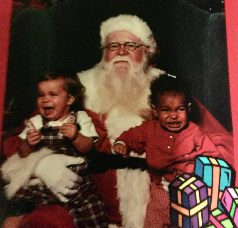 Two crying toddlers sitting on Santa Claus' lap